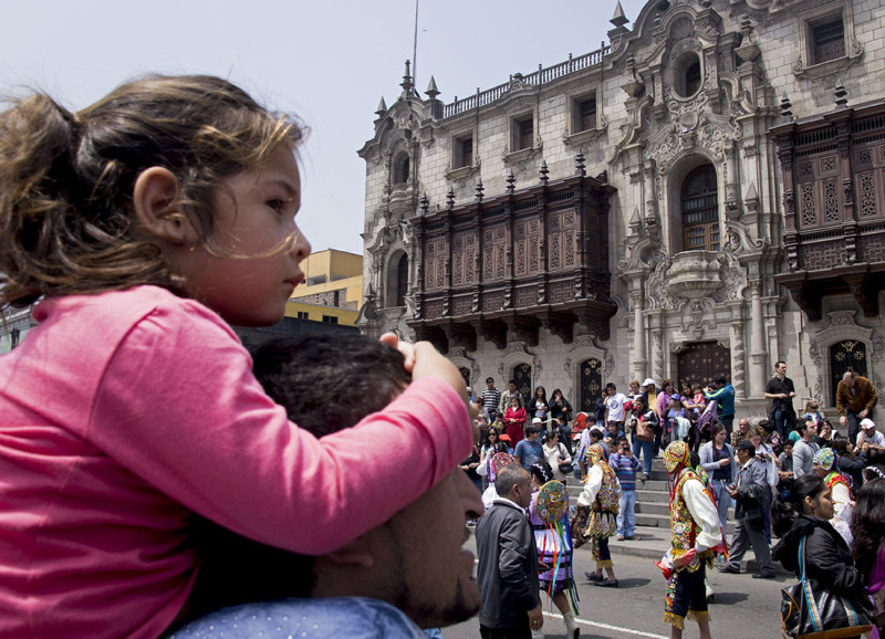 little girl watching parade in Lima
