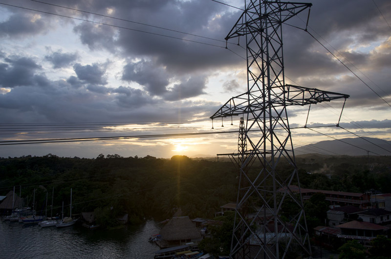 sun sets behind power lines, Rio Dulce, Guatemala